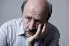 Head portrait of senior mature old man on his 60s looking sad and worried suffering pain and depression in sadness face expression Stock Photos