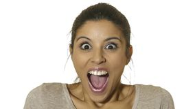 Head portrait of young happy and excited hispanic woman 30s in surprise and astonished face expression eyes and mouth wide open is. Olated on white background in stock photo