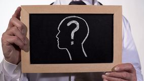 Head with questionmark drawn on blackboard in physician hands, diagnostics. Stock footage royalty free stock photos