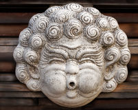 Head sculpture with chubby cheeks. Old, dirty sculpture of a blowing face with strong chubby cheeks Royalty Free Stock Photo