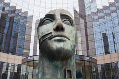 Head sculpture in front of a glass facade Stock Images