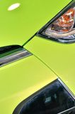Head of sedan in green. Part of a sedan in green, with head lamp, which color and shape is beautiful, shown fantastic design and car manufacturing tecnology Stock Images