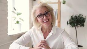 Elderly blond woman teacher makes video call chatting online