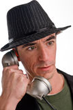 Head and shoulders shot of caucasian male wearing a hat. A head shot of a Caucasian male wearing a pin striped hat and talking on a telephone. He appears to be a Royalty Free Stock Images