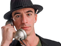 Head and shoulders shot of caucasian male wearing a hat. A head shot of a Caucasian male wearing a pin striped hat and talking on a telephone. He appears to be a Royalty Free Stock Photo