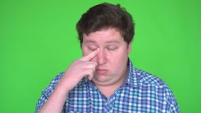 Head shot concept of man got eyes allergy and rub her eyes with finger and blinked. 4k, green screen stock video