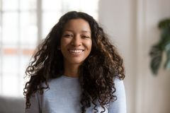 Head shot portrait attractive African American smiling woman. Happy pretty female with fluffy curly hair, successful millennial person, standing, posing in royalty free stock photography