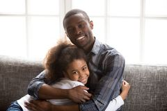 Head shot portrait happy African American family at home. Loving father sincere embracing little preschooler daughter, sitting together on couch in living room stock photography