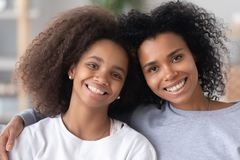 Head shot portrait of happy African American mother and daughter. Head shot portrait of happy excited African American mother and teen daughter, looking at royalty free stock image