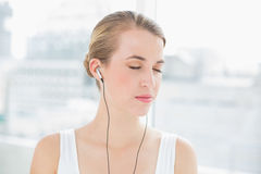 Head shot of relaxed sporty woman listening to music Stock Photos