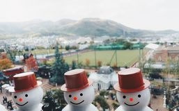 Head shot of 3 smiling snowmen wearing red hat with background o
