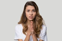 Young woman over grey background cupped hands in praying gesture. Head shot studio portrait millennial woman pose over grey background looking at camera cupped stock photo
