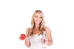 Head shot of woman holding an apple and water against white background Royalty Free Stock Photos