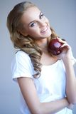 Head shot of woman holding red apple against grey Stock Images