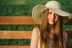 Head shot young woman in park. At hat Royalty Free Stock Image
