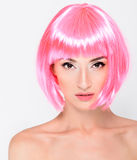 Head shot of young woman in pink wig on white background Royalty Free Stock Photography
