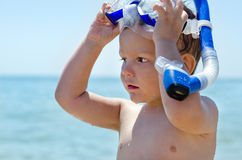 Little boy with goggles and snorkel. Head and shoulder portrait of an attractive little boy with his hands raised removing his goggles and snorkel with an ocean Stock Photography