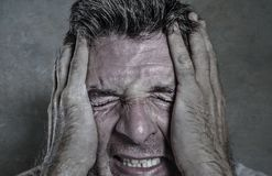 Head and shoulders dramatic portrait of young man crying in pain suffering depression and anxiety problem feeling stressed and. Desperate in looking devastated royalty free stock photography