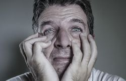 Head and shoulders dramatic portrait of young man crying in pain suffering depression and anxiety problem feeling stressed and. Desperate in looking devastated stock photos