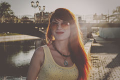 Head and shoulders of ginger hair woman in orange color sunglasses backlit vintage color grading Stock Photography
