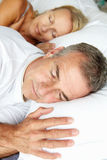 Head and shoulders mid age couple sleeping. Portrait head and shoulders shot of mid age couple sleeping in bed Royalty Free Stock Images