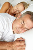 Head and shoulders mid age couple sleeping. In bed Royalty Free Stock Images
