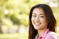 Head and shoulders portrait Asian woman outdoors Royalty Free Stock Photo