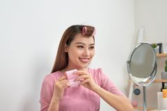 Head and shoulders portrait of beautiful Asian woman wearing hair curlers looking in mirror with wide smile, home interior on royalty free stock images