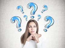 Clever young businesswoman thinking, question mark. Head and shoulders portrait of a beautiful young woman with fair hair wearing white and thinking looking Royalty Free Stock Image