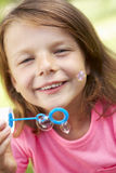 Head And Shoulders Portrait Of Girl Blowing Bubbles Stock Photography