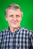 Head and shoulders portrait of mature smiling man, green background Stock Photo