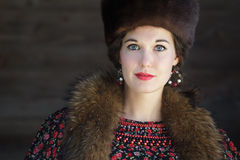 Head and shoulders portrait of Russian beauty with blue eyes wearing fur Cossack hat Royalty Free Stock Photos