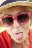 Head And Shoulders Portrait Of Senior Woman Poking Out Tongue Royalty Free Stock Image