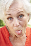 Head And Shoulders Portrait Of Senior Woman Poking Out Tongue Stock Images