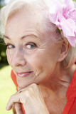 Head And Shoulders Portrait Of Smiling Senior Woman With Flower In Hair Stock Image