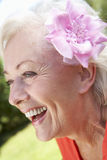 Head And Shoulders Portrait Of Smiling Senior Woman With Flower. In Hair stock images