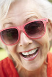 Head And Shoulders Portrait Of Smiling Senior Woman Wearing Sunglasses Stock Photo