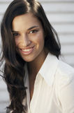 A head and shoulders portrait of a smiling young woman wearing a white shirt Stock Image