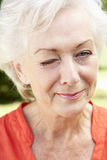 Head And Shoulders Portrait Of Winking Senior Woman Royalty Free Stock Photography