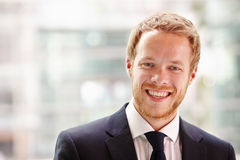 Head and shoulders portrait of a young businessman smiling Royalty Free Stock Image