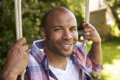 Head And Shoulders Shot Of Mid Adult Man Sitting On Swing Royalty Free Stock Photo