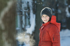 Head and shoulders winter outdoor portrait of cheerful teenage boy breathing with visible steam mouth in frosty sunny day. Head and shoulders winter outdoor stock photography