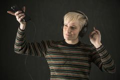 Young blonde woman wearing headphones and enjoying the music. Royalty Free Stock Image