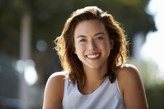 Head and shoulders of young woman sitting outdoors Stock Photos