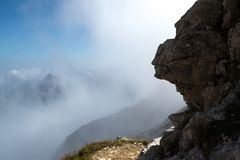 Head silhouette on stone, seen from the side, with clear formations resembling a human nose, lips, eyes and cheeks. Found in the Mangart mountain, Julian Alps stock photos