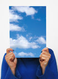 Head in sky. Woman keeping in front of her face a sky with clouds photo stock photos