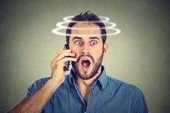 Head is spinning vertigo dizziness. Portrait shocked man talking on mobile phone. Stock Photography