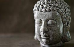 Head statyanseende för Buddha på en mörk stenyttersida Arkivfoton
