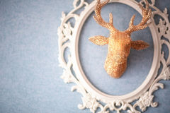 Head of stylized golden reindeer on  wall. Photo of Head of stylized golden reindeer on  wall Royalty Free Stock Images