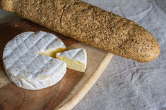 The head of the Swiss Camembert cheese and a triangular piece of cheese on a wooden board and a grain baguette on a woven Stock Photo